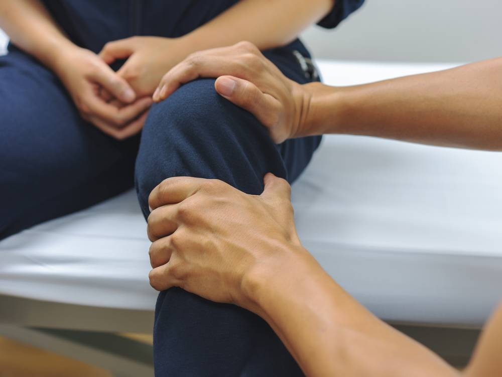 Geste d'un kiné sur le genou d'un patient assis sur la table de massage